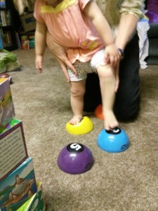 Stepping on targets such as soft stepping stones is a fun activity to practice lifting the foot while the tape assists.