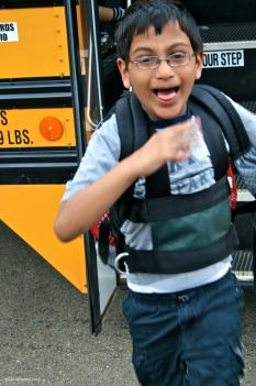Boy getting off of school bus
