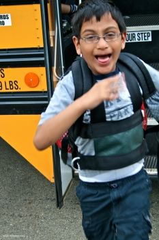 Boy getting off of school bus