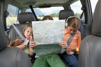3 kids in the car, reading a map, eating and wearing headphones.