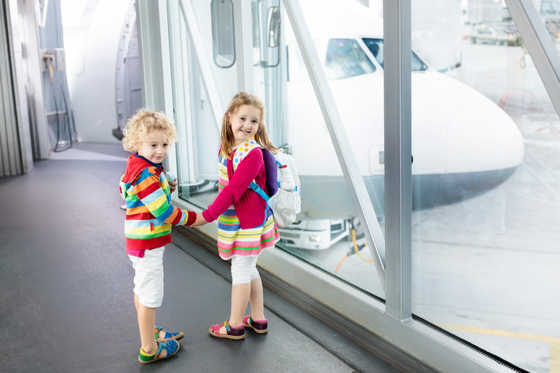 Two children wait to embark on the airplane