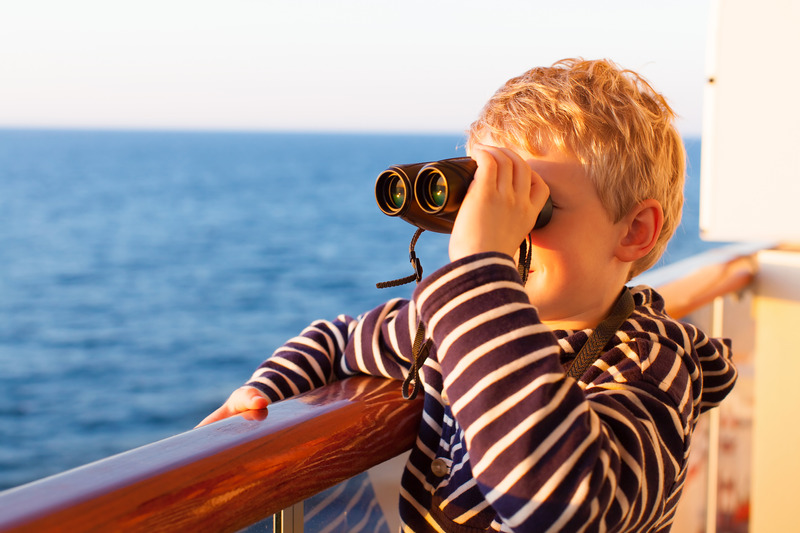 A boy looks over the side of a cruise ship with binoculars