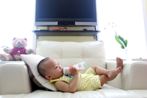 Child laying on couch drinking bottle.